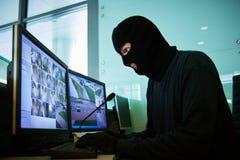 在监视录影监控系统协调的盗案附近的强盗 图库摄影