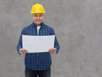 在盔甲的微笑的男性建造者与图纸 免版税库存照片
