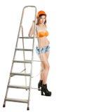 在盔甲的美丽的女性建造者与梯子 库存照片