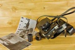 在盖子、照片和影片的老影片照相机木表面上 库存图片