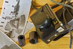 在盖子、照片和影片的老照相机木表面上 库存图片