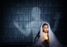 在盖子下的女孩有手电的 免版税库存图片