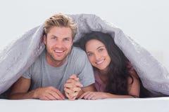 在盖子下的快乐的夫妇 免版税库存图片