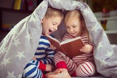 在盖子下的愉快的兄弟姐妹阅读书 免版税图库摄影
