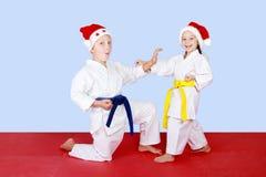 在盖帽做技术空手道的圣诞老人的快乐的孩子 免版税库存照片