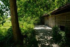 在盖的小屋前的遮荫板条路面与竹子被编织的墙壁 库存照片