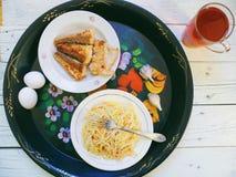 在盘、自创蛋糕、油煎的鱼和一杯茶的面条在桌上的 免版税库存照片