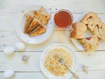 在盘、自创蛋糕、油煎的鱼和一杯茶的面条在桌上的 库存图片