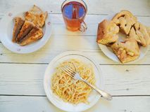 在盘、自创蛋糕、油煎的鱼和一杯茶的面条在桌上的 库存照片