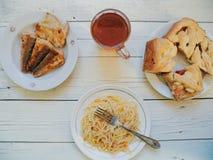 在盘、自创蛋糕、油煎的鱼和一杯茶的面条在桌上的 图库摄影