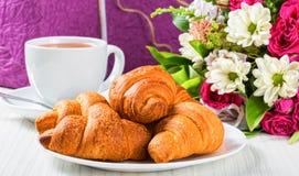 在盘、茶和花束的新月形面包 免版税库存图片