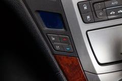 在盘区的中央控制控制台在与气候控制和音象系统的汽车特写镜头和CD的一个孔里面和 库存图片