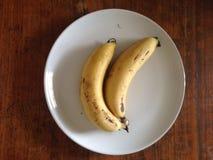 在盘和木头桌上的两个香蕉 免版税库存图片