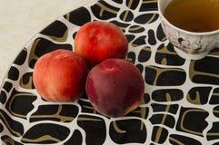 在盘子和一杯茶的桃子 库存图片