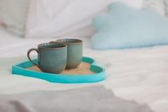 在盘子白色床,早餐概念上的两个杯子 免版税库存图片