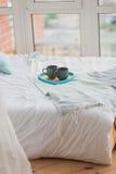 在盘子白色床,早餐概念上的两个杯子 免版税库存照片