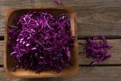 在盘子的切好的红叶卷心菜在木桌上 库存图片