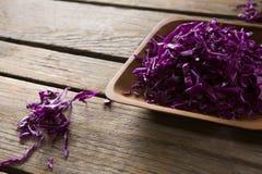 在盘子的切好的红叶卷心菜在木桌上 图库摄影