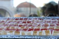 在盘子的土耳其快乐糖有一个清真寺的被弄脏的剪影的在背景中在番红花城  免版税库存照片