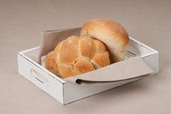在盘子的小圆面包有在自然亚麻制背景的餐巾的 免版税库存图片