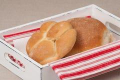 在盘子的小圆面包有在自然亚麻制背景的餐巾的 库存照片