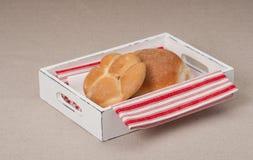 在盘子的小圆面包有在自然亚麻制背景的餐巾的 库存图片