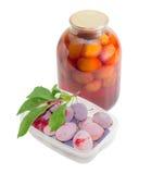 在盘子的新鲜的李子和在玻璃瓶子的罐装李子 图库摄影