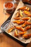 在盘子的油煎的土豆切片有开槽的杓子的 免版税库存照片
