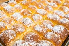 在盘子的热的被烘烤的黄油面包新近地洒与糖粉 免版税库存图片