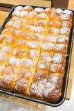 在盘子的热的被烘烤的黄油面包新近地洒与糖粉 库存图片