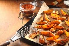 在盘子的热的辣土豆楔子有开槽的杓子的 免版税库存图片