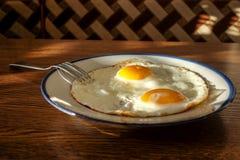 在盘子的煎蛋有浅兰的盛肉盘的 免版税图库摄影