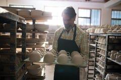 在盘子的男性陶瓷工杯子 免版税图库摄影