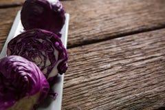 在盘子的红叶卷心菜在木桌上 库存图片