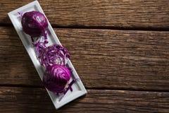 在盘子的红叶卷心菜在木桌上 库存照片