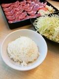 在盘子的饭碗和新鲜的猪肉切片和微笑鱼丸服务用圆白菜,设置了膳食,午餐集合 免版税图库摄影