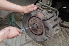 在盘式制动器的汽车修理师工作 库存照片