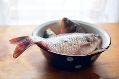 在盘或碗的鱼在桌上在厨房里 免版税库存图片