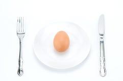 在盘的一个未加工的新鲜的鸡蛋与叉子和刀子 库存图片