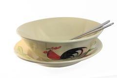 在盘的一只鸡和A碗陶瓷与匙子和叉子 库存图片