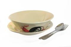在盘的一只鸡和A碗陶瓷与匙子和叉子 免版税库存图片