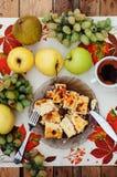在盘的乳酪砂锅用在一把木背景、刀子和叉子,果子,早晨,可口早餐, autum的绿色葡萄 库存照片