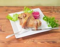 在盘的被烘烤的火腿飞腓节与绿色和辣根酱 免版税库存照片