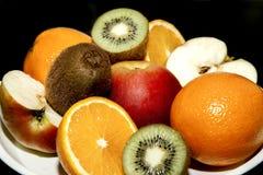 在盛肉盘桔子苹果猕猴桃的果子 库存照片