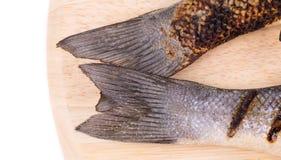 在盛肉盘的两条烤雪鱼尾巴 库存图片