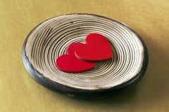 在盛肉盘的两红色心脏 图库摄影
