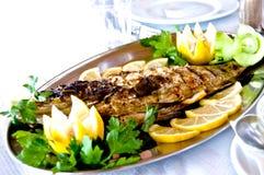 在盛肉盘的油煎的鱼 库存照片