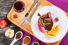 在盛肉盘的烤鸭子腿有杯的红葡萄酒 图库摄影