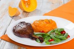 在盛肉盘的烤鸭子腿用菠菜和南瓜粥 免版税库存照片