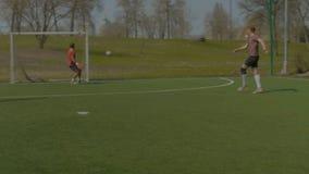 在目标的年轻足球运动员射击在训练期间 股票录像